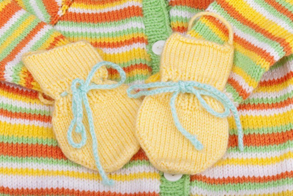 Babysachen selberstricken - gerade in den letzten Wochen der Schwangerschaft hat man dazu häufig Zeit. Hier: handgestrickte Babyhandschuhe auf einer selbstgestickten Babyweste. (#01)